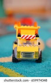 POZNAN, POLAND - JUNE 14, 2017: Yellow Lego construction truck on carpet in soft focus