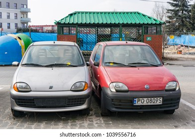 Poznan, Poland - March 03, 2018: Parked red and gray Fiat Seicento car on parking spots. Gray car misses license plate.