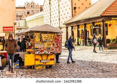 Poznan, Poland - March 1, 2020: Small stand selling souvenirs and gifts on the old city square. Sunny day in the winter season. Surface is made of old cobblestones.