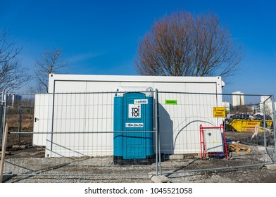 Poznan, Poland -  March 11, 2018: Toi Toi portable toilet and container on a construction area behind a metal fence