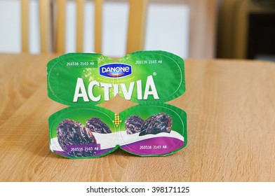 POZNAN, POLAND - MARCH 18, 2016: Four pack of Danone Activia yogurt with dry plums on wooden background