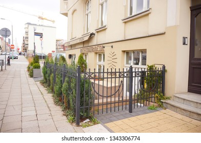 Poznan, Poland - March 19, 2019: Front entrance with door of the Oskoma restaurant surrounded with a metal fence and green trees by a sidewalk on the Mickiewicza street.