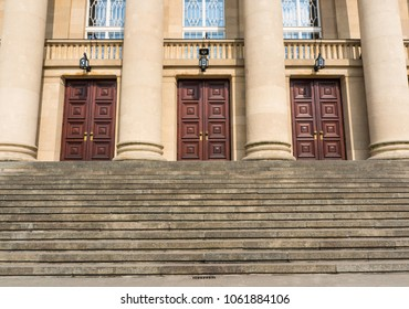 Poznan, Poland - March 26, 2018: Stairs leading to three wooden doors of the Grand Theatre building on the Fredry street