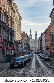 Poznan, Poland - March 8, 2015: Street with parked cars and old buildings leading to a cathedral