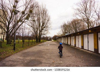 Poznan, Poland - March 9, 2019: Young boy riding a bike along row of garage doors at a park on a cloudy day.
