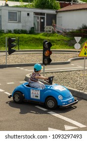 Poznan, Poland - May 1, 2018: 4 years old boy driving a small blue electric car on a practicing track at the Malta park
