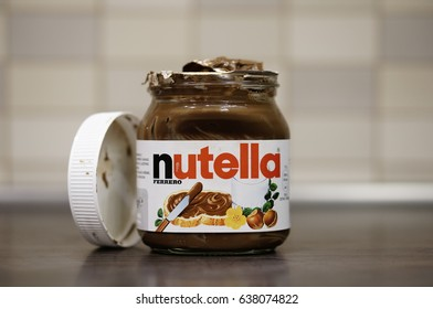 POZNAN, POLAND - MAY 11, 2017: Opened glass jar of Nutella hazelnut and chocolate spread on wooden table