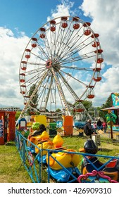 POZNAN, POLAND - MAY 15, 2016: Ferris wheel and duck cart attraction on a luna park on a sunny day