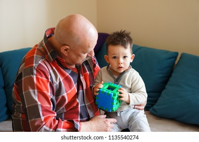 Poznan, Poland - May 16, 2015: Bald older man holding a young toddler boy with plastic toy cube in a living room