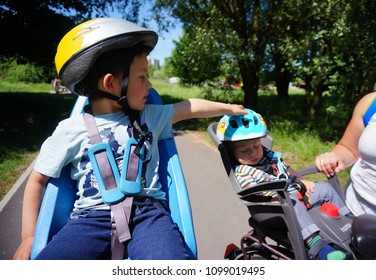 Poznan, Poland - May 20, 2018: Boy and baby in safety seats on bicycles at a park on a sunny day