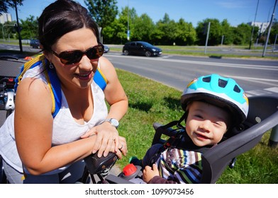 Poznan, Poland - May 20, 2018: Woman with sunglasses close to a baby boy with safety helmet in a bicycle seat