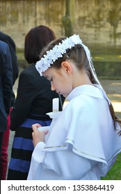 Poznan - Poland / May 22 2016, Young girl in white alba clothing is waiting amongst guests outside the Church on a day of her First Holy Communion