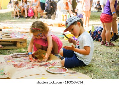 Poznan, Poland - May 27, 2018: Boy and girl painting on paper with water color and a brush on a Kindernalia event at the Jan Pawla II park