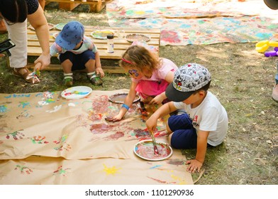 Poznan, Poland - May 27, 2018: Boy and girl painting on a large piece of paper with water color on a Kindernalia event at the Jan Pawla II park on a sunny day
