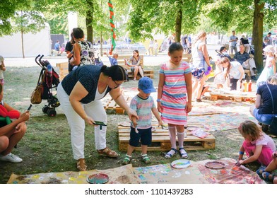 Poznan, Poland - May 27, 2018: Children standing with painting brush by a large piece of paper on the Kindernalia event on the Jan Pawla II park