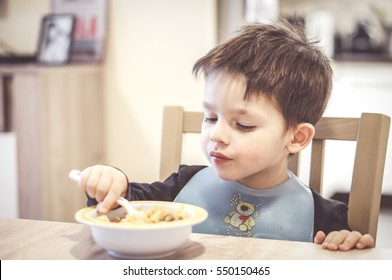 POZNAN, POLAND - NOVEMBER 19, 2016: Unidentified two years old child eating from a bowl with a plastic toddler bib by a table