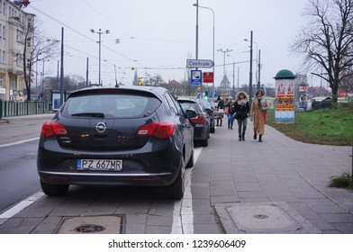 Poznan, Poland - November 22, 2018: Parked Opel Astra car next to sidewalk with walking people in the city center.