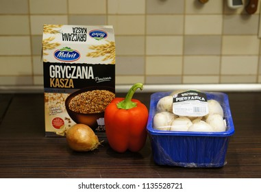 Poznan, Poland - November 28, 2015: Porridge, white onion, red pepper and champignons in a wooden table