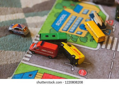 Poznan, Poland - November 4, 2018: Mix of toy cars laying on a play road mat on the floor in soft focus.
