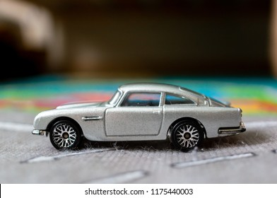 Poznan, Poland - September 9, 2018: Gray Mattel Hot Wheels toy Aston Martin on a mat. The staging is simulating a car driving on a road.