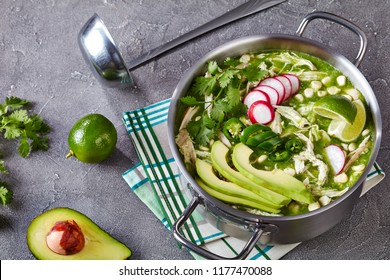 Pozole Verde in a metal casserole - Mexican stew filled with shredded chicken and hominy in a warm green chile broth garnished with radish slices, cilantro and a lime