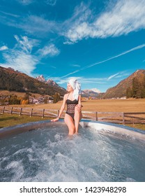 Pozza di Fassa, Italy - October 25, 2018: A girl at QC Terme Dolomiti relaxing in a thermal bath spa outdoor