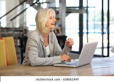 P{portrait of happy older business woman working on laptop