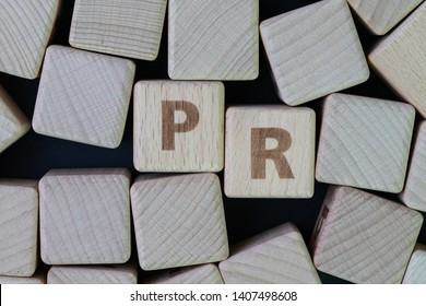 PR, public relation company or corporate communication concept, cube wooden block with alphabet combine the word PR on black chalkboard background.