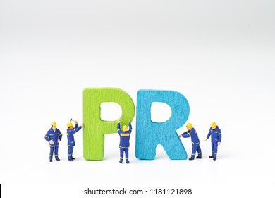 PR, Public Relations concept, miniature people staff help building color wooden letters forming word PR on white background with copy space, spread of information from organization to the public.