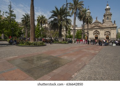 Praca de Armas, information plate on the floor, large palms and in the background Metropolina church and Episcopal palace complete the beauty of the place, Santiago city, Chile, October 2015.