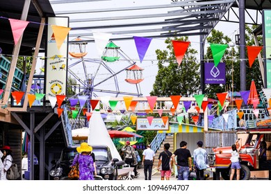 Prachuap Khiri Khan Province, THAILAND - APRIL 6, 2018: Crowd walk in vintage market with colorful flag decorate above on wooden building, Ferris wheel, old car, bicycle,