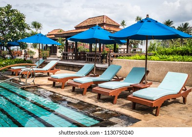 Prachuap Khiri Khan Province, Thailand - June 26, 2018 : View of the beach chairs with canvas umbrellas near the swimming pool at the beach of the sea in Dusit Thani Hua Hin Hotels & Resorts