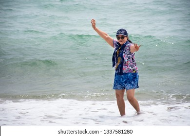 PRACHUAP KHIRI KHAN, THAILAND - JANUARY 30 : Asian thai old women travel posing for take photo and playing in the sea at the Ban Krut Beach on January 30, 2018 in Prachuap Khiri Khan, Thailand