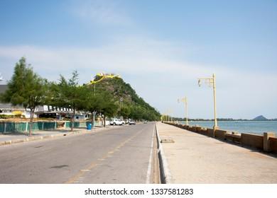 PRACHUAP KHIRI KHAN, THAILAND - JANUARY 30 : View landscape and traffic road beside seascape with Wat Khao Chong Krachok temple on mountain on January 30,2018 in Prachuap Khiri Khan, Thailand
