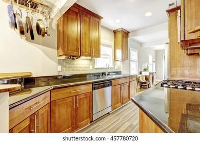 Practical kitchen room interior. Cabinets, granite tops and hanging pot rack. Northwest, USA