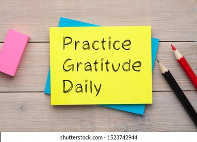 Practice Gratitude Daily written on the note with colorful pencils and eraser aside on wooden desk.