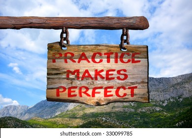 Practice makes perfect motivational phrase sign on old wood with blurred background