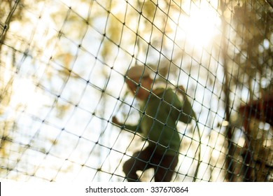 practice nets playground. boy plays in the playground shielded with a protective safety net. concept of children on line, kid in social networks. blurred background, blurred motion due to the concept
