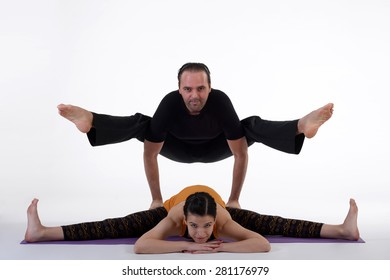 Practicing acro yoga exercises in group. People doing yoga exercises in studio on white background.
