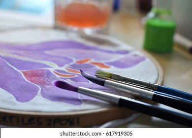 Practicing silk painting, stained paint brushes lean against silk in an embrodery hoop , shallow depth of field, bottles of  paint in background, art and crafts hobby