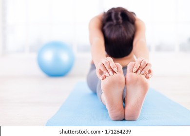 Practicing yoga. Beautiful young woman stretching on yoga mat