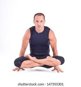 Practicing Yoga exercises. ??n doing  Yoga exercises in studio on white background.  Pose name: Scale Pose - Tolasana