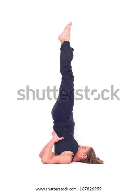 Practicing Yoga exercises. Young  woman doing  Yoga exercises in studio on white background.  Pose name: Shoulderstand - Sarvangasana - Viparita Karani