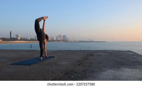 Practicing yoga facing the sea at dawn