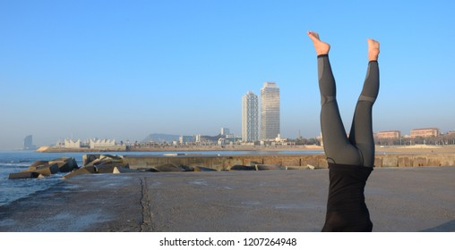 Practicing yoga facing the sea at dawn in Barcelona city