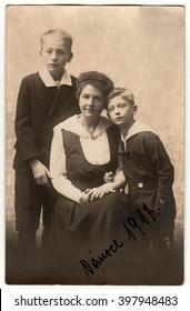PRAGUE, AUSTRIA-HUNGARY - CHRISTMAS, 1917: Vintage photo shows mother with children (boys). Black & white antique photography.