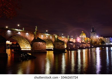 Prague by Night. The iconic Charles Bridge join the old and new sides of this Bohemian city. The lights play on the Vltava River at night and the statues that line the bridge are among the most photog