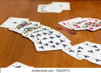 Prague, ca. July 2017 - Cards lying on wooden table during a rummy like card game. Very long sequence of clubs and some other melds. No decks in view