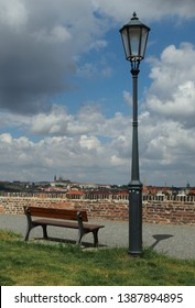 Prague Castle and old lamp and bench - view from Vysehrad fortress. Lonely bench and lamp in Prague with beatiful view to Prague downtown and Hradcany castle with st. Vitus cathedral. Vertical photo.