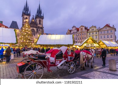 Prague Christmas market on the night in Old Town Square. Tyn Church, Bohemia. Blurred people on the move. Prague, Czech Republic.